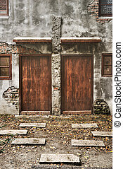 Creepy scenic of old house with two closed wooden door.