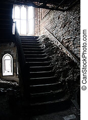 a dark stairwell of an abandoned building in ruins