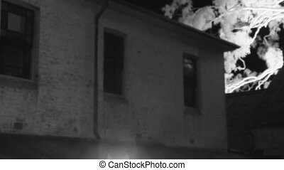 Creepy windows of a haunted house - A medium shot of a...