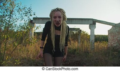 Portrait of bloodthirsty creepy woman vampire hissing furiously, showing bloody face and teeth, expressing aggression and danger while walking on ruins of abandoned building at twilight in countrysdie