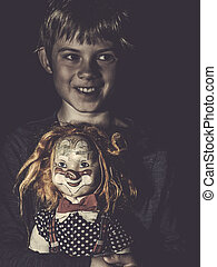 Creepy young boy with scary doll