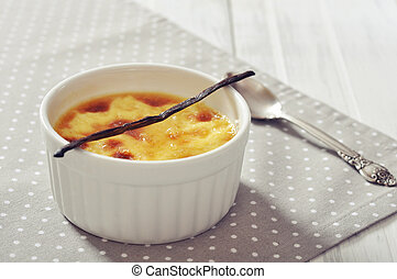 The creme brulee in ceramic baking mold with vanilla pod on wooden table