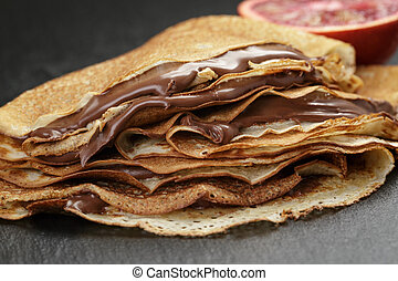 crepes or blinis with chocolate cream and orange on slate ...