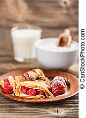 Crepes with berries and chocolate topping
