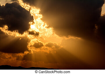 Crepuscular rays from floating clouds with sun at sunset