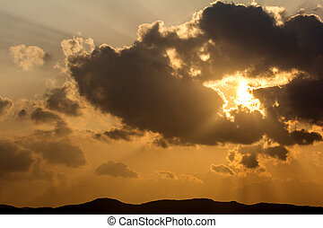 Crepuscular rays from floating cloud covering the sun at...