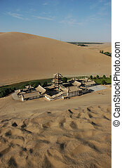 Oasis with temple amid desert dunes in Turpan, China