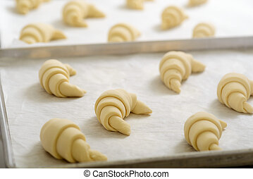 Crescent rolls laying on a metal tray before baking