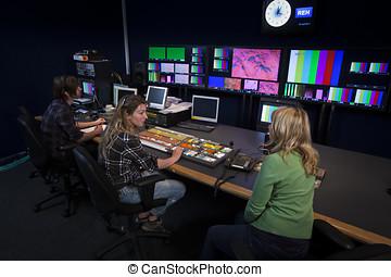 Crew in TV Broadcast Gallery - TV Director talking to her...