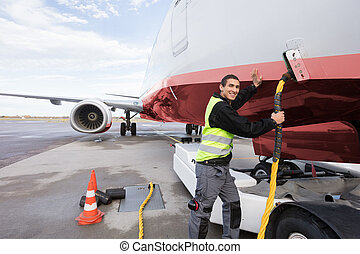 Crew Member Charging Airplane On Runway