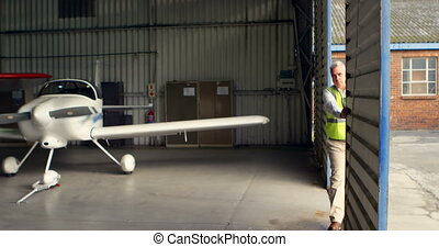 Crew member opening the door of aerospace hangar 4k