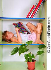 criança, lendo um livro, em, um, estante de livros