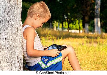 criança menino, tocando, com, pc tabela, ao ar livre, com, floresta, experiência, jogo computador, dependência, conceito
