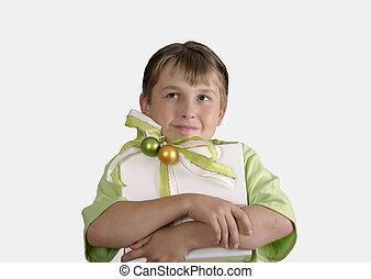 criança, segurando, um, embrulhado presente, e, pensativamente, olhar