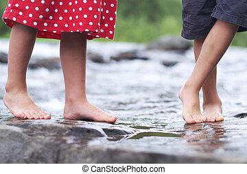 crianças, encharcar pés, em, um, riacho