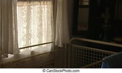Crib and curtain shot - A medium shot of a curtain and crib....