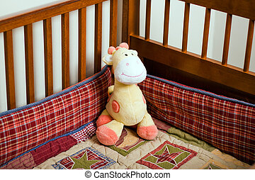 Crib Giraffe - Yellow stuffed animal giraffe in empty baby...