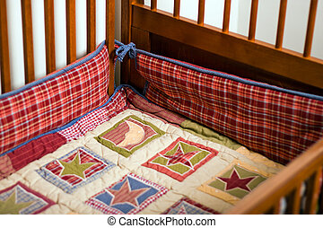 Crib Inside - Comforter and bumper in empty baby crib
