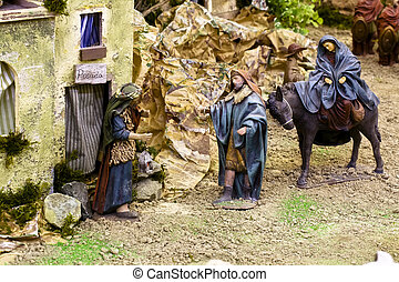 Crib scene - Joseph, looking for cover for Virgin Mary,...