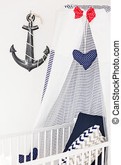 Crib with canopy in nautical nursery