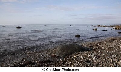 Criccieth beach and sea lapping rocks North Wales UK -...