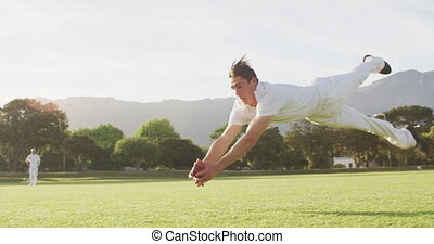 Front view of a Caucasian male cricket player wearing whites on a cricket pitch, diving for the ball and catching it during a match on a sunny day, in slow motion