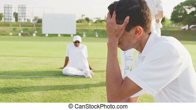 Side view of a disappointed teenage mixed race male cricket player wearing whites, sitting on the pitch, holding his head after the match on a sunny day, with other players in the background, slow motion