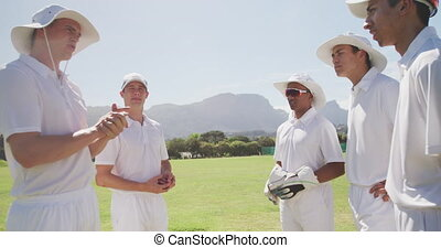 Side view of a group of teenage multi-ethnic male cricket players wearing whites, standing on a cricket pitch, discussing the game on a sunny day, in slow motion