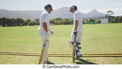 Cricket players doing a check on a pitch - Side view of two ...