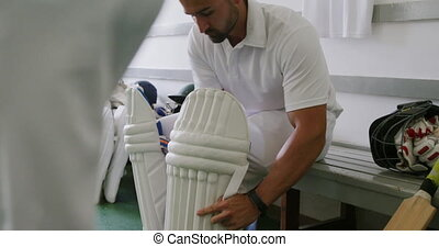 Cricket players preparing in the locker room - Side view of ...