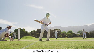 Side view of a teenage Caucasian male cricket player wearing a helmet and holding a cricket bat, trying to hit the ball on the pitch, with an Asian player in the background squatting, trying to catch the ball during a cricket match in slow motion