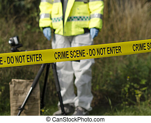 Detective checking for evidence behind a crime scene barrier