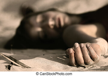 crime scene - woman playing dead, lying in the sand