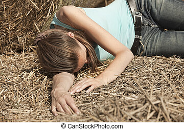 Crime scene - young woman lying unconscious in the field