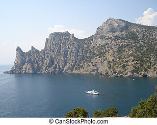 Crimea mountains and Black sea landscape. Yacht in the bay