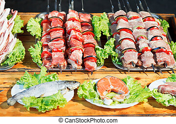 skewers of shishkebabs and raw fish for grill