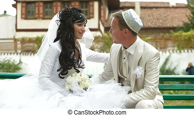 Crimean Tatar newlyweds sitting in the park Bakhchisaray...