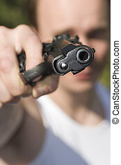 Criminal - A man holding a gun and pointing it at the camera...