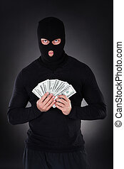 Criminal in a balaclava holding a fistful of money ...