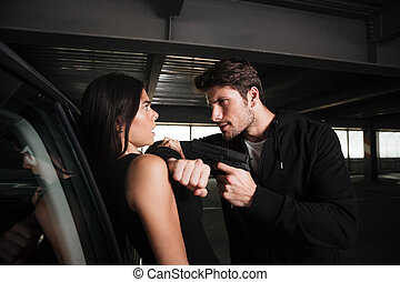 Criminal man standing and threatening to frightened young woman