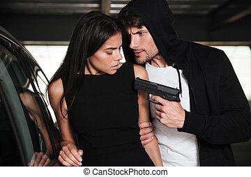 Criminal man threatening to woman with gun on car parking