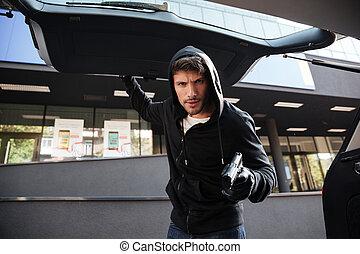 Criminal man threatening with gun and closing car trunk outdoors