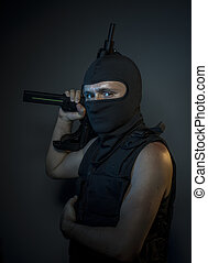 Criminal, Terrorist, a man dressed in a bulletproof vest and balaclava, is armed with pistols and machine guns