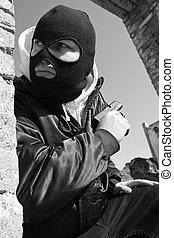 Criminal with a gun hiding
