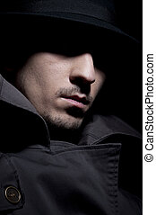 Criminal - young criminal in shadow, isolated on a black ...