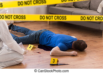 criminalist collecting evidence at crime scene -...