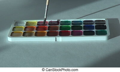 crimson maroon color. Artist works with brush and watercolor...
