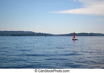 A sail boat with crimson sails at lake Washington, mount Raineer in a haze