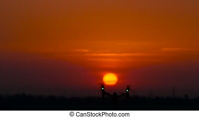 Crimson sunset, a copter flies on its background and disappears in the distance