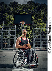 Cripple basketball player in wheelchair holding ball.